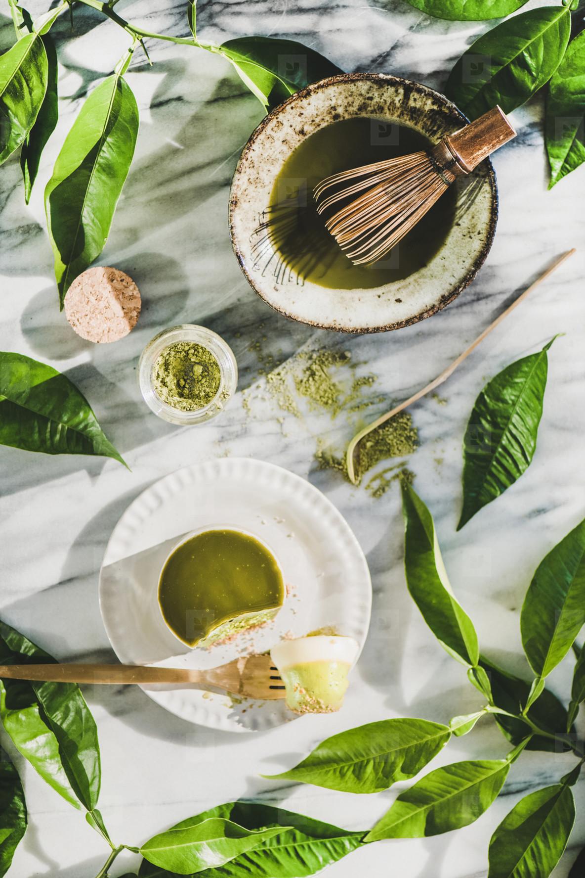 Flat lay of green matcha cheesecake dessert and matcha powder