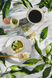 Flat lay of green matcha cheesecake and black coffee in cup
