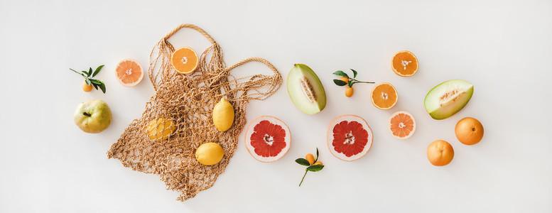 Flat lay of summer natural net bag and various fresh fruits