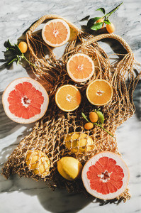 Flat lay of summer net bag with fresh citrus fruits  close up