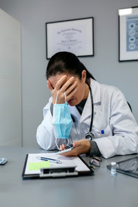Worried female doctor with hands on face