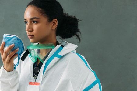 Young medical worker holding a respirator wearing a protective suit and looking away