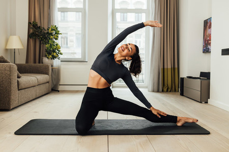 Smiling woman in sport clothes doing stretching workout on mat