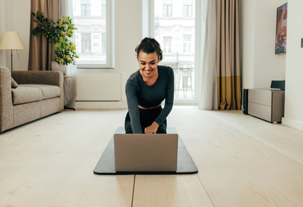 Woman in sportswear sitting on floor and using a laptop