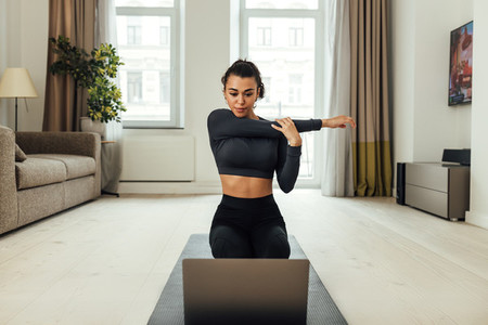 Young woman repeating exercises while watching online exercise session on her laptop