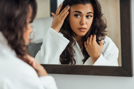 Middle East woman looking at mirror reflection taking care of her skin