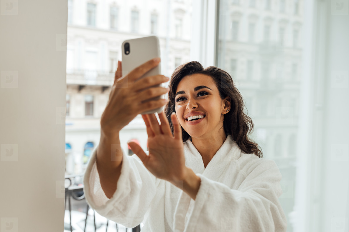 Happy beautiful woman taking a selfie on a balcony in her hotel room  Smiling female in bathrobe holding smartphone and making photographs