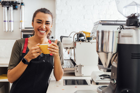 Laughing coffee shop owner standing at counter holding a mug  Happy woman in apron