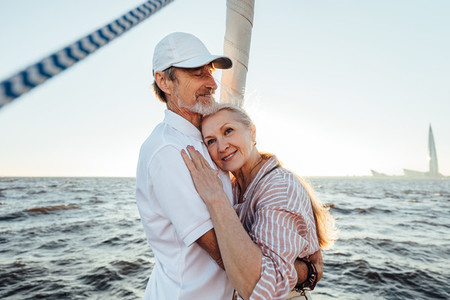 Mature husband and wife embracing each other at sunset on the yacht Senior woman with her head on husbands chest looking away