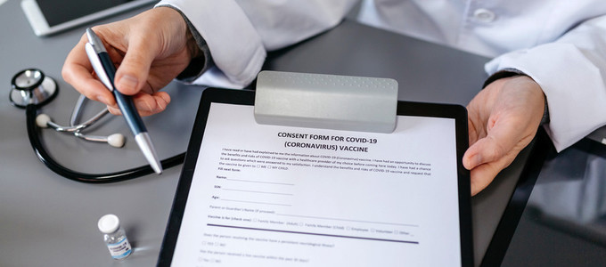 Unrecognizable doctor showing consent form for coronavirus vacci