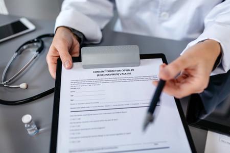 Unrecognizable doctor offering pen to sign coronavirus vaccine c