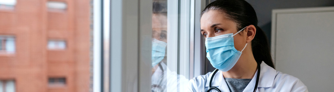 Female doctor looking out the hospital window