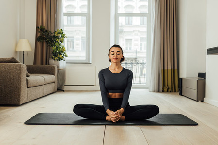 Young woman in sports clothes meditating on a mat