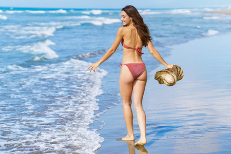 Woman in swimwear and sunhat enjoying the beach on her holiday
