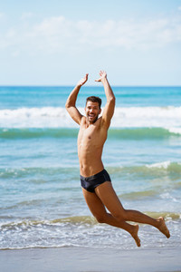 Young man with beautiful body in swimwear jumping on a tropical beach
