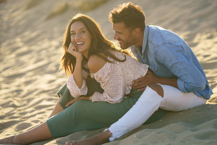 Young couple laughing together sitting on the sand of the beach