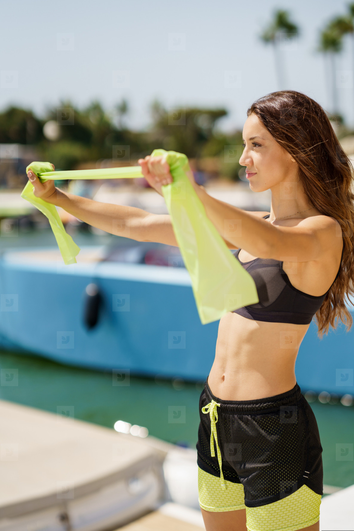 Fitness woman in sportswear outfit working out with a elastic band on waterfront harbour