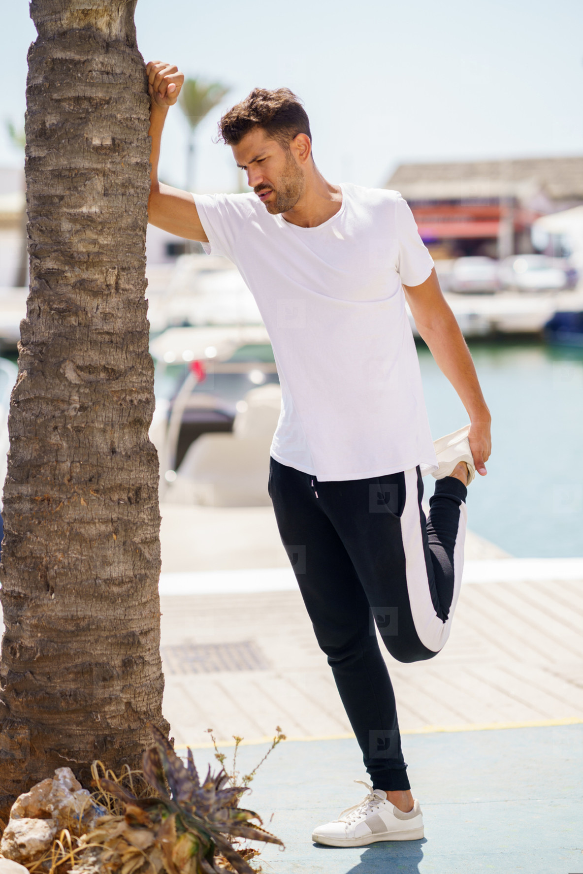 Man stretching after exercise in a harbour