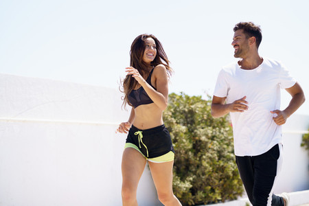 Young beautiful couple training together running outdoors