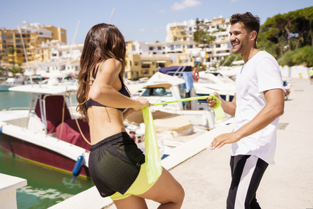 Couple in sportswear outfit working out with a elastic band on waterfront harbour