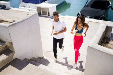 Athletic couple training hard by running up stairs together outdoors