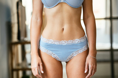 Unrecognizable female with a beautiful belly wearing blue lingerie