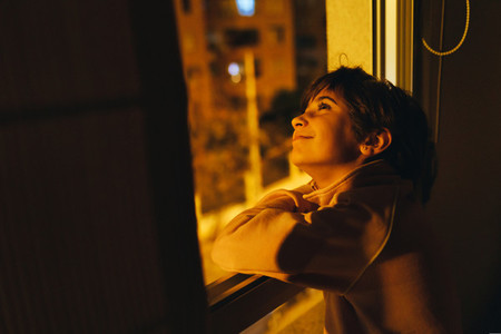 Girl looking out window at night to see the moon and stars