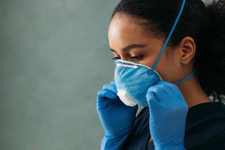 Close up of young nurse adjusting respirator