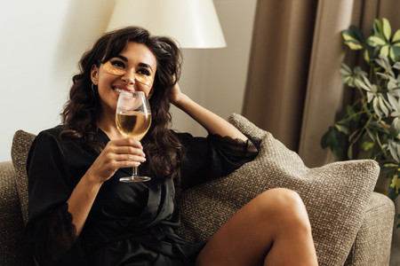 Happy woman with bocal of wine sitting on a sofa at home