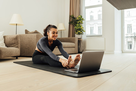 Smiling woman in sportswear sitting on a mat in front of a laptop
