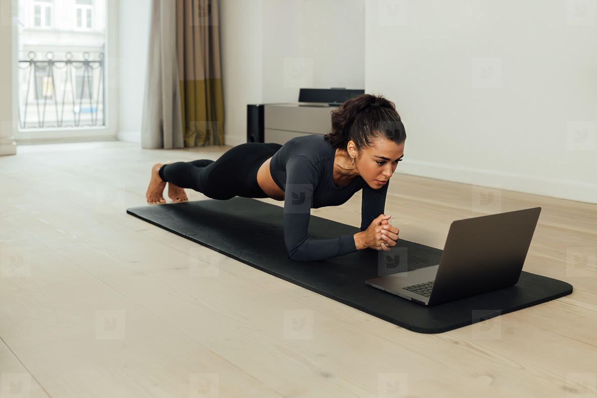Young fit woman doing plank on mat