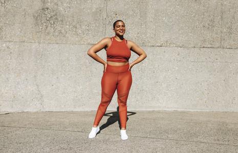 Healthy woman in sportswear standing outdoors
