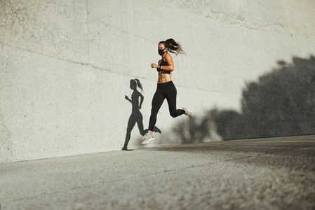Athletic woman running wearing protective face mask
