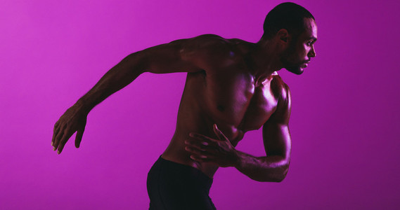 Fit athlete working out on purple background