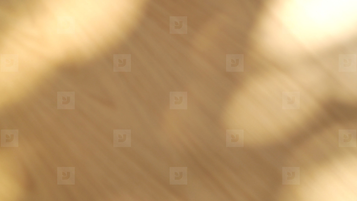 Abstract blurred sunlight natural shadow overlay on wooden table