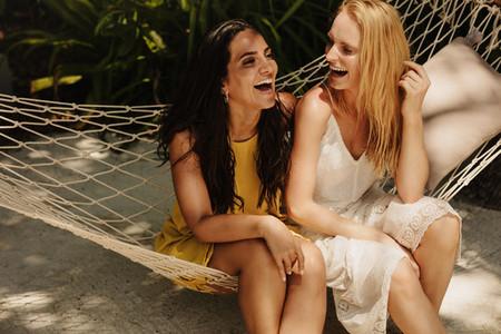 Happy women friends sitting in a hammock