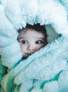 Little baby wrapped up with a warm green blanket
