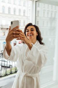 Happy woman in bathrobe taking selfie on smartphone
