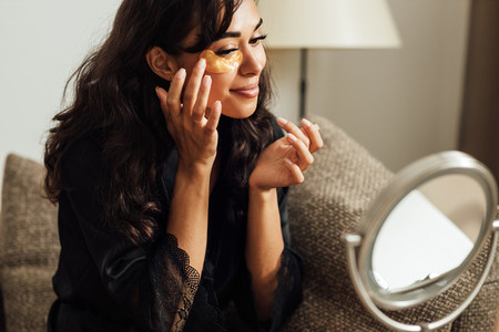 Young woman doing a skincare beauty routine at home in front of a mirror