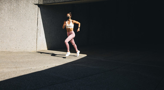 Woman jogging in the morning wearing a face mask