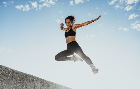 Fitness woman jumping from wall