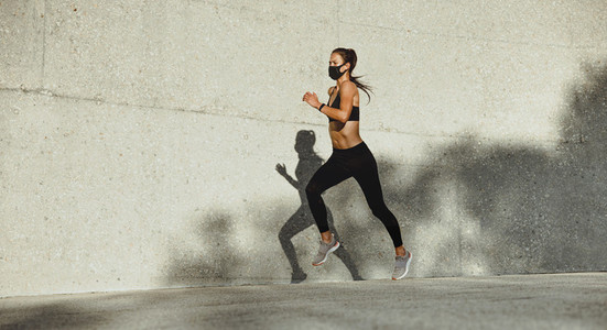 Woman on a morning run with face mask