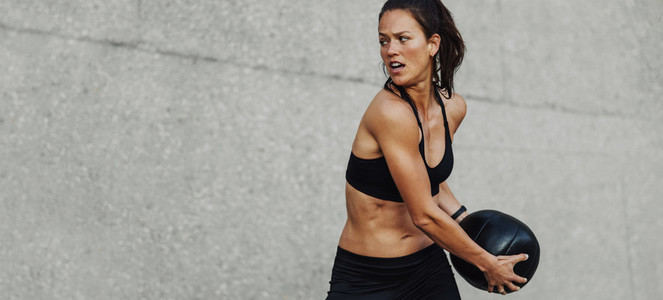 Fitness woman doing workout holding a medicine ball