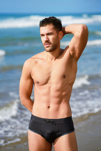 Young athletic man with fitness body standing on the beach