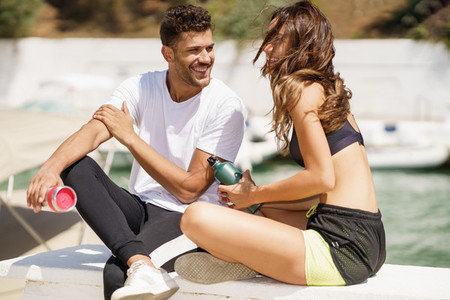 Two fitness people hydrate themselves with water in metal cans while taking a break after sport