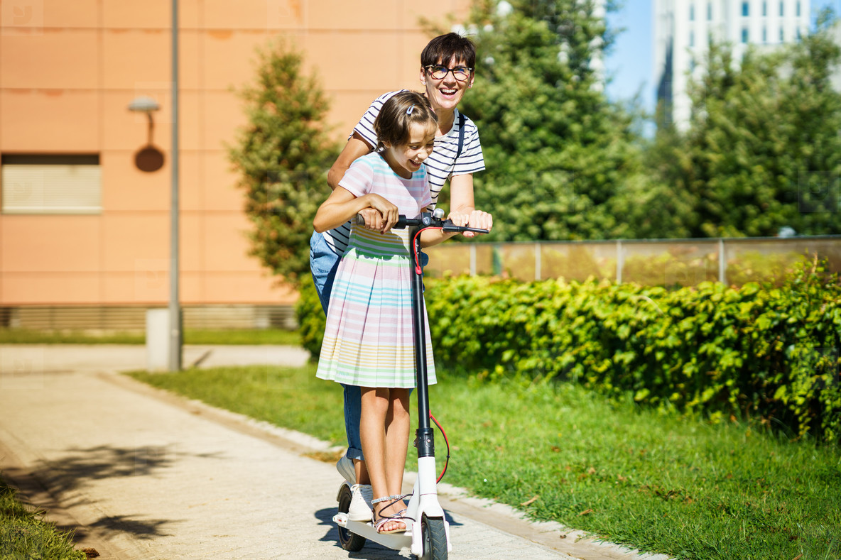 Mother and daughter riding on electric scooter