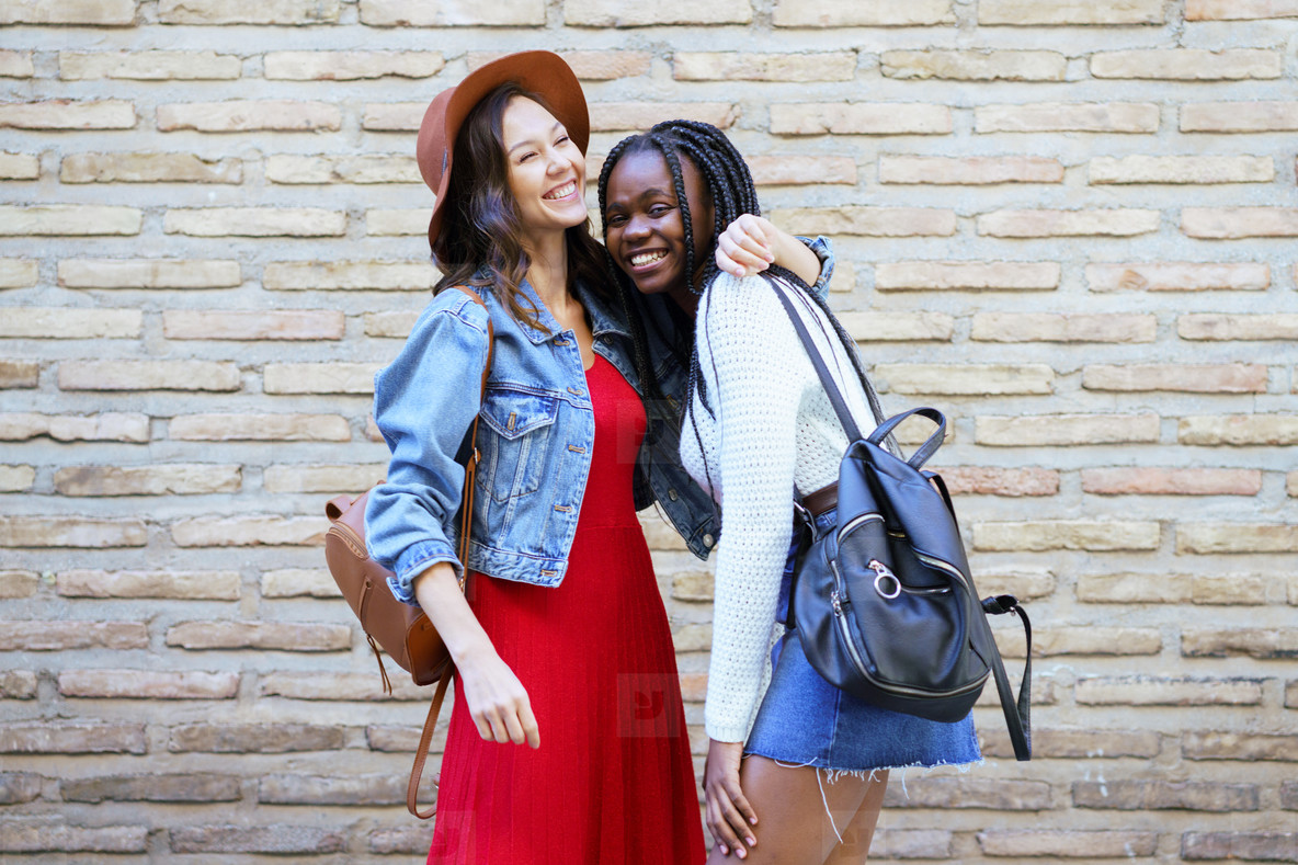 Two friends hugging in urban background    Multiethnic friends