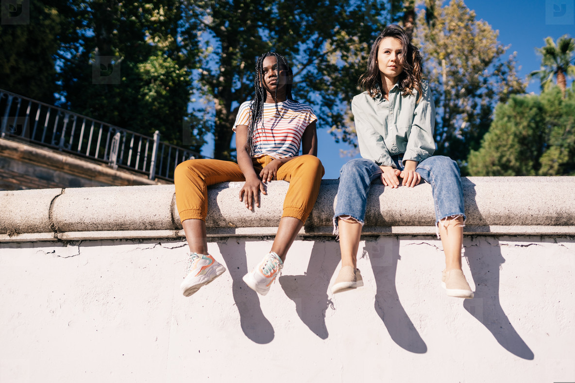 Two multiethnic women sitting on a urban wall