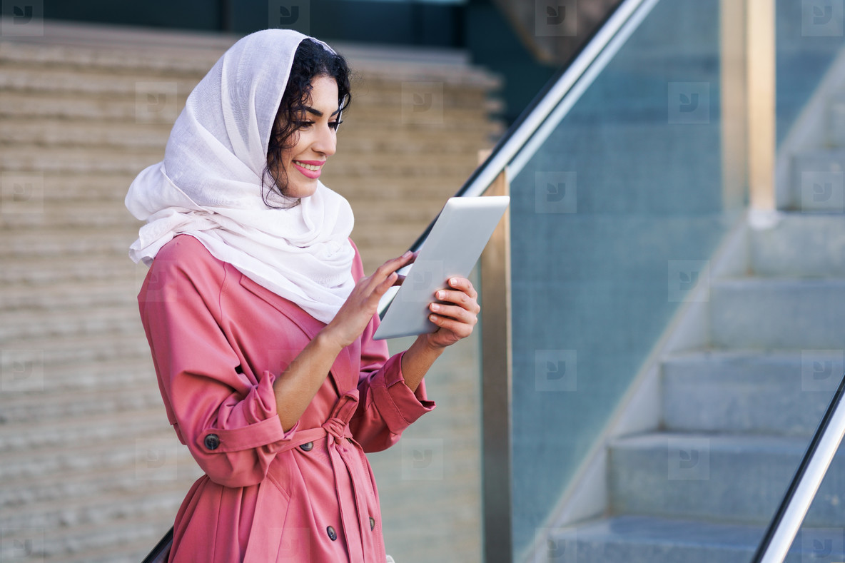 Young Muslim woman wearing hijab using digital tablet outdoors