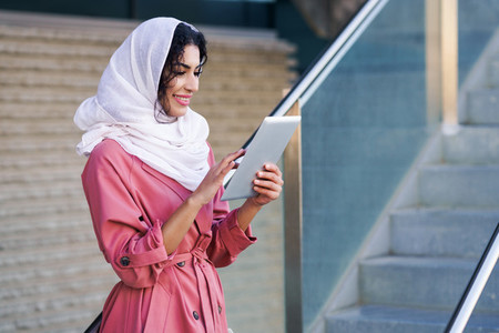 Young Muslim woman wearing hijab using digital tablet outdoors